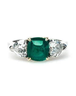 Mint Julep is a stunning contemporary (circa 1980's) ring made from platinum and 18k yellow gold. This bold ring features a unique, bright green sugarloaf cabochon emerald gauged at 2.60ct., accompanied with a Guild Laboratories certificate that states the emerald has color and inclusions typical of emeralds from Colombia. Mint Julep's center stone is flanked by two prong-set heart shaped diamonds gauged at approximately 1.00ct, graded E-F color and VS clarity. This ring is finished off with scrolling metalwork inside the basket and a highly polished shank. Mint Julep is currently a size 6.75 and can be sized to fit.