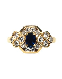 Thousand Oaks is a chic, contemporary (circa 1980's) ring made from 18k yellow gold, centering a prong-set Oval Cut natural sapphire gauged at approximately 0.50ct. The center sapphire is surrounded by a geometric, heart-shaped frame of sixteen Round Brilliant Cut diamonds with an estimated weight of 0.65ct graded F-G color and VS clarity, finished off with a highly polished, comfortable shank. Thousand Oaks is currently a size 5 and can be sized to fit!