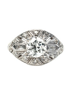 Apple Valley is a tasteful Art Deco diamond engagement ring made from platinum centering a 0.90ct EGL certified Old European Cut diamond graded I color and VS1 clarity. This beautiful diamond is box-set and hugged on either side by twelve round Single Cut diamonds and two Baguette Cut diamonds totaling approximately .20ct. Apple Valley is the epitome of Art Deco design detailed with a stunning geometric pattern and complete with milgrained edges. Apple Valley is currently a size 5.5 and can be sized to fit.