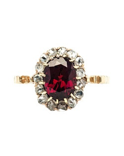 Elk Ridge is a whimsical antique Victorian era ring made from 14k yellow gold centering an oval, deep brownish-red garnet gauged at approximately 1.75ct. The center garnet rests within a fifteen prong setting and is surrounded by fifteen dazzling Rose Cut diamonds with a total approximate weight of 0.40ct. This beautiful halo ring pairs the drama of a cocktail ring with the delicate proportions of an engagement ring. Elk Ridge is currently a size 6 and can be sized to fit.