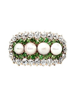 Hermitage is an incredible Victorian era 14k yellow gold ring composed of four natural pearls with a beautiful creamy and slightly rose colored hue gauged at 4mm each. These beautiful pearls are surrounded by twenty-eight electric green demantoid garnets and framed by a sparkling halo of twenty-four Old European Cut diamonds totaling about 1.00ct. Consider the amazing task the original jeweler accomplished by sourcing these rare gems; the demantoids were most likely from the mountain rivers of Russia, the natural pearls from the waters of Japan, and the diamonds from India. This ring is a truly special addition to our collection. Hermitage is currently a size 5 and can be sized to fit.