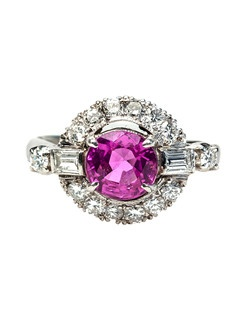 Cherry Lane is a beautiful example of 1950's design! This gorgeous ring is made from platinum and centers a four prong-set 1.12ct round pink sapphire accompanied with a Guild Laboratories certificate stating that the sapphire is heat treated. A stunning halo of fourteen Round Brilliant Cut diamonds and two Baguette Cut diamonds further enhance the beautifully saturated center stone, totaling exactly 0.42ct. This ring is finished off with scrolling filigree along the gallery of the ring. Cherry Lane is currently a size 4 and can be sized to fit.