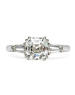 Southwick is an exceptional vintage-inspired engagement ring made from platinum featuring a striking 2.05cts GIA certified Asscher Cut diamond graded G color and VVS2 clarity. This classic three stone ring showcases the center stone elegantly set between two tapered baguettes weighing approximately 0.50ct with F-G color and VS clarity. Southwick's beautiful filigree blends seamlessly with scrolled engraving throughout the shank and basket. Southwick is currently a size 6.5 and can be sized to fit.