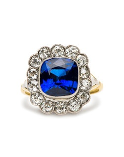 High Grove is a stunning Belle Epoch antique sapphire engagement ring made from platinum topped with 18kt yellow gold. This show stopping antique Edwardian era ring features a heated natural 2.99ct GIA certified Cushion Cut sapphire that is delicately surrounded by a halo of fourteen bezel set Old European Cut diamonds with an approximate weight of 1.40cts. Prong set and further accented with milgraining and a hint of handmade filigree throughout the basket, this sapphire and diamond ring is truly exquisite. This ring can be sized to fit.