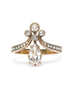 Trumpet & Horn's exclusive Tiara ring is reminiscent of Victorian times when jewelry and fashion were inspired by nature and romance. This unique diamond ring is made from 18k yellow gold. The ring pictured features a 0.70ct EGL certified pear shaped diamond with E color and SI1 clarity. A trio of bezel set Single Cut diamonds balance this gorgeous prong set center diamond. Further accents of bead set Single Cut diamonds on the shoulders are enhanced with delicate milgrained edges. This ring is made to order.