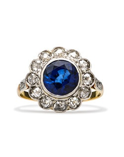 Essex is an exquisite Victorian cluster ring made from 18k yellow gold and platinum featuring a stunning round natural Ceylon sapphire certified by Guild Laboratories and estimated to weigh 2.50ct. A hand made bezel setting cushions this bright blue sapphire surrounded by a blazing cluster of twelve Old Mine Cut diamonds with a total approximate weight of 1.32ct, graded H-J color and I1 clarity and further decorated with two Rose Cut diamonds on each side of the shank. This ring can be sized to fit.