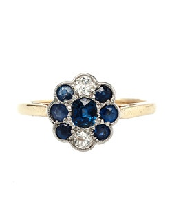 Birmingham is a lovely Edwardian era platinum topped 18k yellow gold ring that lays very flat on the hand. An oval shaped cluster of seven bright blue natural sapphires totaling about 0.70ct. is the focal point of this ring, accented by two Old European Cut diamonds adorning the top and bottom of the ring with an estimated total weight of 0.20ct. Birmingham is finished with subtle milgrained edges and stamped with English Hallmarks on the inside shank. Birmingham is currently a size 6.75 and can be sized to fit.
