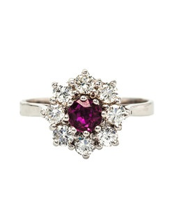 Apple Hill is a pretty Mid Century 14k white gold ring centering a single round, deep red natural ruby gauged at 0.45ct framed by a decadent halo of eight Round Brilliant Cut diamonds totaling approximately 0.65ct graded H-I color and VS clarity. Apple Hill is currently a size 5.5 and can be sized to fit!