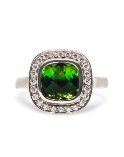 Paisley is a dramatic vintage Modern era halo ring made from 18k white gold centering a bezel set Fancy Cushion Cut green tourmaline gauged at 8.00mm x 8.15mm.  This unique and inexpensive engagement ring showcases a halo of twenty-four Round Brilliant Cut diamonds with a total approximate weight of 0.50ct graded H-I color and VS clarity. Two bezel set Round Brilliant Cut diamonds weighing a total of 0.04ct are set on each side of the basket to add a lovely extra detail to this ring.