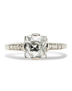Stratford is an antique Edwardian diamond engagement ring made from platinum centering a 2.05ct EGL certified Old Mine Cushion Cut diamond with E color and SI2 clarity. This simple, easy to wear ring showcases the colorless, sparkling main diamond accented by a channel of eight bead set Full Cut round diamonds with a total approximate weight of .20ct.