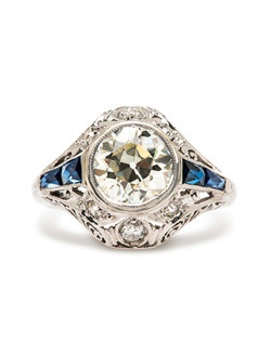 Potomac is an incredible vintage Art Deco era diamond and sapphire engagement ring featuring a 1.58ct EGL certified Old European Cut diamond graded L color and VS2 clarity. Nestled between two tapering rows of bright blue sapphires, this enchanting diamond is enhanced by six Old European Cut round diamonds with a total approximate weight of .18ct. Delicate filigree work and hand engraved flowers surround each diamond. This ring can be sized to fit.