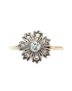 Goldwater is a beautiful 14k yellow and white gold ring from the 1960's designed in the shape of a simple seven petal flower centering a bezel set Transitional Cut diamond gauged at 0.15ct. Seven Single Cut diamonds totaling approximately 0.35ct. decorate each petal of the flower, finished off with a simple knife-edge 14k yellow gold shank. Goldwater is currently a size 7.25 and can be sized to fit.