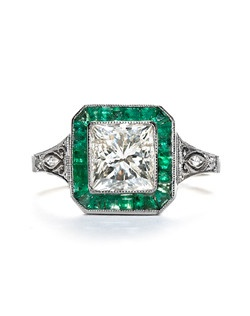 Raleigh is a newly manufactured, vintage-inspired diamond and emerald engagement ring that recreates a beautiful antique setting in a modern way. This ring is made from platinum and features an EGL appraised Rectangular Modified Brilliant Cut diamond. The diamond was evaluated within the setting and is estimated to weigh 2.01cts with J-K color and SI3 clarity. It is surrounded by a square border of small Calibre Cut emeralds and is further enhanced by a dramatic tapered shank set with small Full Cut diamonds accented with engraving and filigree. Raleigh is currently a size 7. and can be sized to fit.