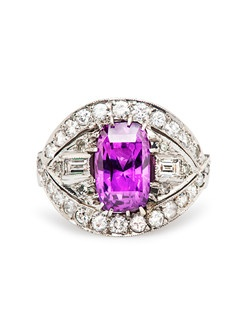 Pike Road is a vintage Modern era purple sapphire and diamond ring made from 18k white gold. The delicate prong set EGL certified natural, heated Oval Cut purple sapphire weighs exactly 5.26cts. The magnificent center stone is bordered by thirty two Round Brilliant Cut diamonds and two Baguette Cut diamonds with a total approximate weight of 1.10cts, graded G-H color and SI clarity. This show stopping cocktail style engagement ring is further accented with milgrained edges and romantic filigree throughout the basket. This ring can be sized to fit.