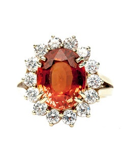 Squaw Valley is a fabulous modern 18k yellow gold cocktail ring centering a stunning orange spessartite garnet gauged at approximately 6.00ct. accompanied with a Guild Laboratory certificate stating the garnet is of natural color with no clarity enhancements. A beautiful halo of fourteen Round Brilliant Cut diamonds surround the center stone totaling approximately 1.40ct., graded F-G color and VS clarity. This show-stopping cocktail ring is complete with a simple split shank. Squaw Valley is currently a size 7 and can be sized to fit.
