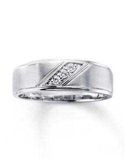The brushed finish of this handsome men's wedding band is highlighted by a diagonal stripe of three round diamonds adding a touch of eye-catching style. Totaling 1/10 carat in diamond weight, the ring is crafted in 10K white gold.