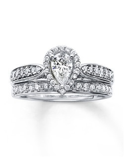 A pear-shaped diamond is framed in round  diamonds at the center of the engagement ring in this awe-inspiring bridal set. Additional round diamonds are set in the band of 14K white gold to complete the look. The stunning matching wedding band features a line of glittering round diamonds. The bridal set has a total diamond weight of 1 1/5 carats.