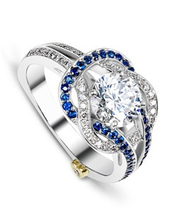 The Entangle engagement ring contains 49 diamonds totaling 0.245ctw and 41 sapphires totaling 0.205ctw. Center stone sold separately, not included in price. Available in yellow, white, or rose gold, and platinum. Rings can be custom made to fit any size or shape diamond or color center stone.
