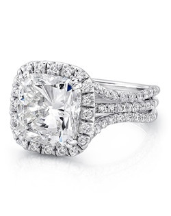 """Elegant cushion-cut diamond halo engagement ring in luxurious platinum, designed to fit an imposing 4.20-carat center, featuring 99 round brilliants (combined weight of 0.84 carats) pave set along the halo and in three rows down the imposing ribbon-like triple shank that Uneek's award-winning Silhouette Collection is known for; this style can accommodate a range of center stone sizes (beginning at 0.50 carats), available by special order; this style can accommodate different center stone cuts, available by special order