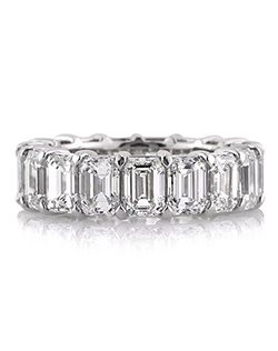 Spurn the traditional engagement ring with this extraordinary emerald cut diamond eternity band. It features a whopping 9.40ct of perfectly matched emeralds prong set on platinum. Our master jeweler hand sets each hand picked stone to perfection and crafts the ring in a manner that is comfortable for everyday wear. It's your ultra modern engagement ring!