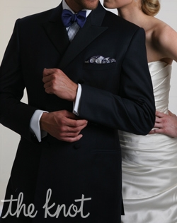 Two to three-button double-breasted Edwardian style tuxedo features midnight super 120s Australian Merino wool and grosgrain peak lapel.